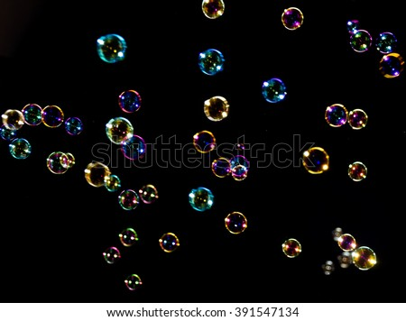 The transparent, iridescent soap bubbles isolated on black. Background - stock photo