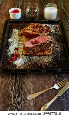 The trendy expensive steakhouse chef prepared a piece of pork tenderloin in the oven, the meat turned out medium rare places with blood for gourmets, the meat will cook the sauce of red berries - stock photo