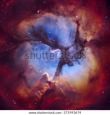 The Trifid Nebula (Messier 20 or NGC 6514) is an H II region located in Sagittarius. The object is an unusual combination of an open cluster of stars. Elements of this image furnished by NASA. - stock photo