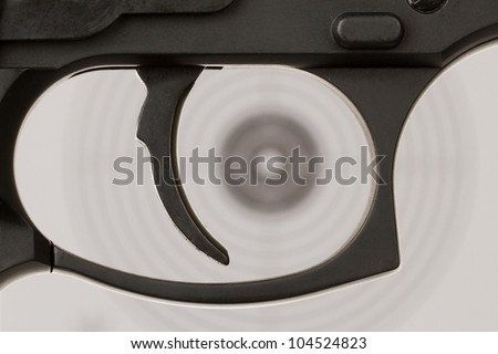 The trigger of a handgun with a shooting target on the background