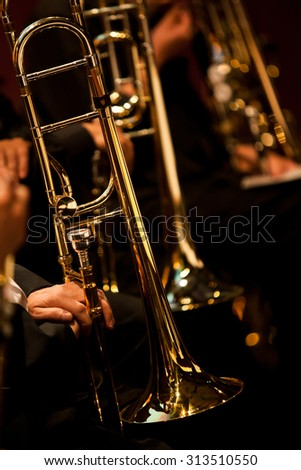 The trombones in the hands of the musicians on the stage in dark colors - stock photo