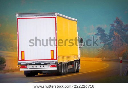 The truck on a highway. Picture with space for your text.