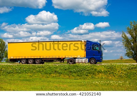 The truck with an awning goes on the way to a sky background with clouds and a green grass.