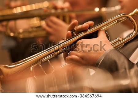 The trumpet in the hands of a musician in the orchestra closeup - stock photo