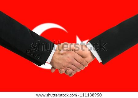 The Turkish flag and business handshake - stock photo