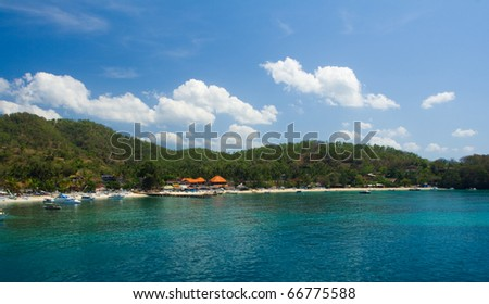 The turquoise water of the port village of Padang Bai, home to the ferry to Lombok in Bali, Indonesia. - stock photo