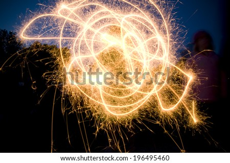 The twists and swirls of a sparkler light the darkness. - stock photo