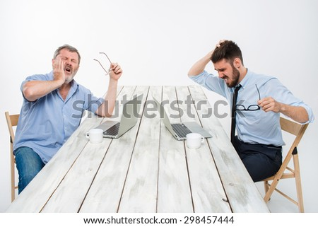 The two colleagues working together at office on white  background. both are looking at the computer screens. both very upset. concept of negative emotions and bad news - stock photo