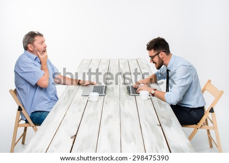 The two colleagues working together at office on white  background. both are looking at the computer screens. one man receiving good news, others are getting some bad news
