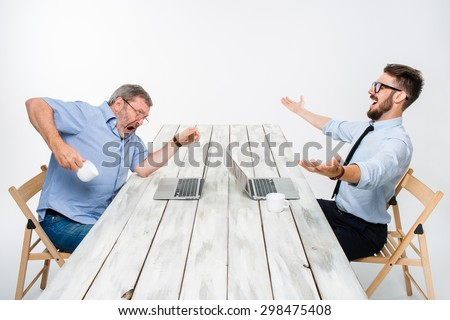 The two colleagues working together at office on white  background. both are looking at the computer screens. one man receiving good news, others are getting some bad news - stock photo