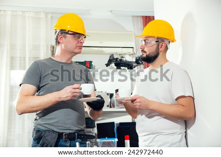 The two craftsmen working together and drink coffee - stock photo