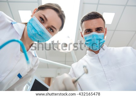 The two dentists in dental office making treatment looking at camera in clinic - stock photo