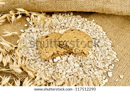 The two halves of biscuits made from oats and berries on a pile of oatmeal, oat stalks on burlap and wooden board - stock photo