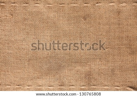 The two horizontal stitching on the burlap as background - stock photo