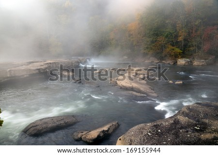 The Tygart River cascades over rocks at Valley Falls State Park in Fairmont, West Virginia, fog over the river in the morning at sunrise - stock photo