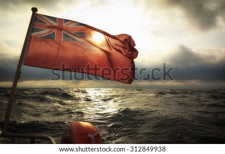 The UK red ensign the british maritime flag flown from yacht sail boat, stormy dark clouds sky and baltic sea. Summer and travel voyage - stock photo