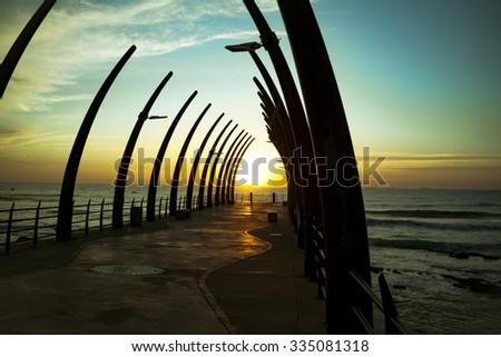 The Umhlanga Pier In Durban South Africa in the Sunrise over horizon of Indian Ocean - stock photo