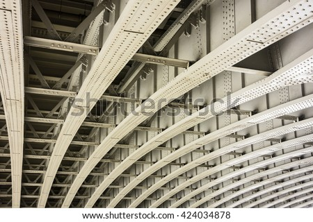 The underside of a bridge in London shows the architectural details of a geometric pattern of curved beams and girders that provide infrastructure support for the road abovve.