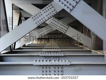 The underside of a bridge with large steel girders, bolts and nuts