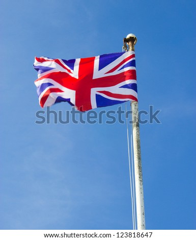 The Union Jack Flag flying from a Flagpole against blue sky. National flag of Great Britain and Northern Ireland