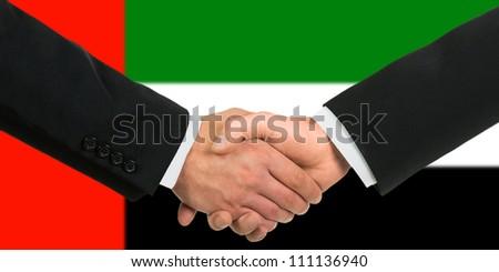 The United Arab Emirates flag and business handshake - stock photo