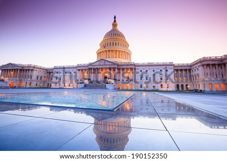 The United States Capitol building with the dome lit up at night.