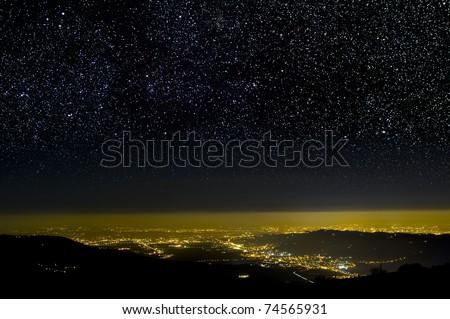 The Universe above city lights. The dark night sky. - stock photo