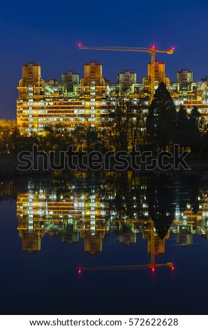 The University Hospital (Uniklinik) Aachen at night with reflection in a small lake. The hospital is one of the biggest in Europe and looks rather like an industrial plant.