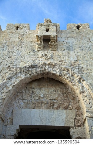 The upper part of Zion Gate, one of the seven gates of the old city of Jerusalem. There are many bullet holes that are clearly seen on the stone. - stock photo