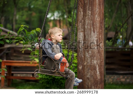 The upset, sad boy sitting on a wooden bench - stock photo