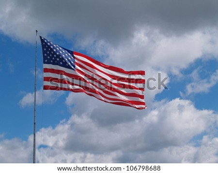 The US American red, white and blue flag flying in front of a blue cloudy sky. - stock photo