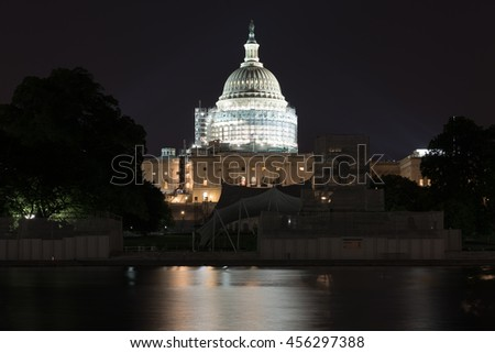 The US Capitol Building under scaffolding as seen across the reflecting pool at night in Washington, DC.