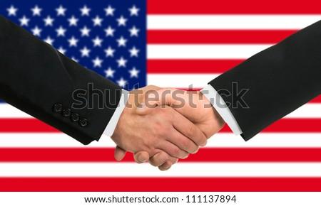 The USA flag and business handshake - stock photo