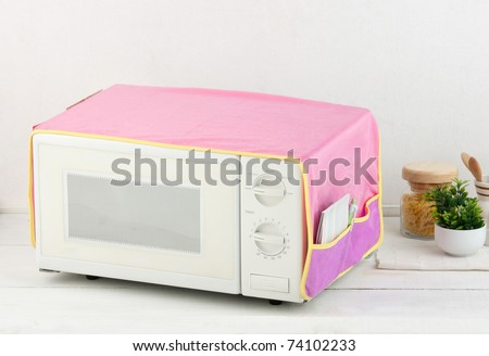 The used microwave oven with the cover blanket to protect dust or dirty - stock photo
