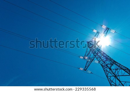 the utility pole of a high voltage line with sun and blue sky. energy supply by power line.