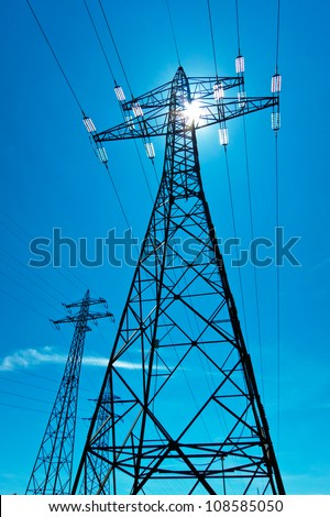 the utility pole of a high voltage line with the sun and blue sky. energy supply from power line. - stock photo