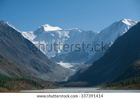 the valley and lake among very high snow peaks
