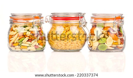 the various raw pasta in a glass jar, isolated on white background - stock photo