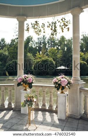 The vases with flowers  are on the alcove