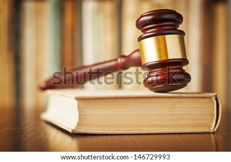The verdict - a wood and brass judges gavel resting upright on top of a thick law book in a court