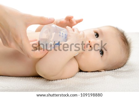 the very  beautiful  little baby drink of  bottle, lie on white background, isolated - stock photo