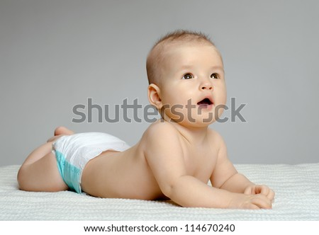 the very  beautiful  little baby , lie on stomach and crawling, on grey background - stock photo