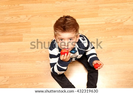 The very handsome, cute and clever boy dressed in classical style clothes s taste strawberries - stock photo