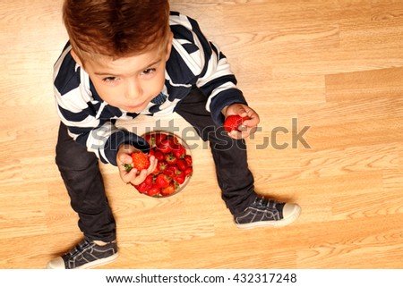 The very handsome, cute and clever boy dressed in classical style clothes  taste strawberries - stock photo