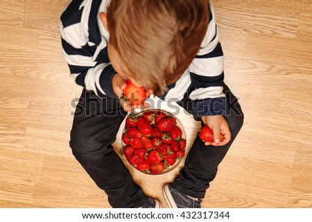 The very handsome, cute and clever boy in classic style suit eats red strawberries. - stock photo