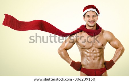 the very muscular  bronzed handsome sexy Santa Claus in red muffler, smile - stock photo