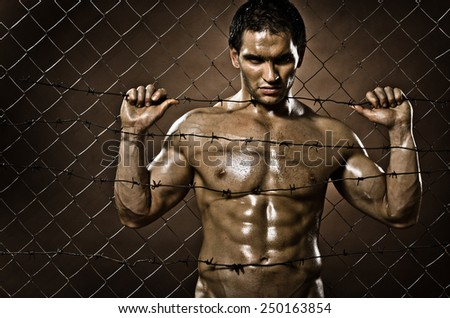 the very muscular handsome felon guy ,  out of netting   steel fence - stock photo
