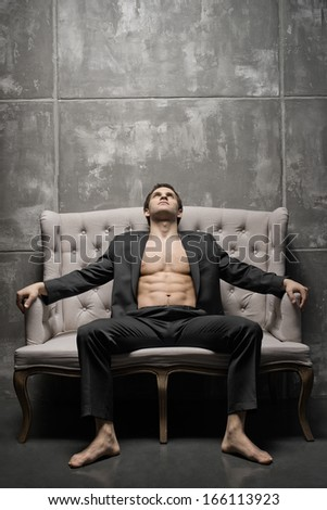 the very muscular handsome sexy guy in black  suit indoor