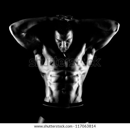 the very muscular handsome sexy guy on black background, naked  torso,  black-and-white - stock photo