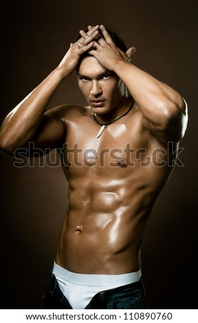 the very muscular handsome sexy guy on dark  brown background, naked  torso